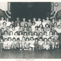 Several children sitting or standing in rows. They are flanked by camp counselors.