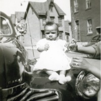 Little girl in a white dress sitting on the car's hood.