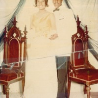 A man in a white jacket and a woman in a holiday dress standing in front of antique chairs.