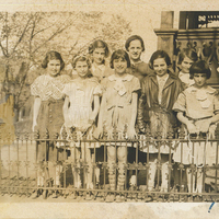 Several girls and women standing in front of a fence in two rows.