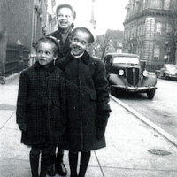 Two girls wearing winter coats standing in front of a woman.