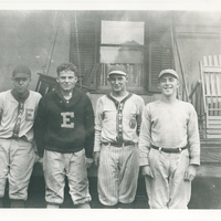 Four men standing next to each other in front of a house. They are all wearing Easton baseball uniforms.