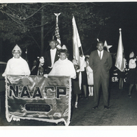 A group of individuals marching. Some are holding various flags. Two women at the front of the group hold a sign indicating the Easton branch of the NAACP.