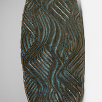 An oblong ceramic slab with repeating wavy lines reminiscent of an abstract hillside carved into it.