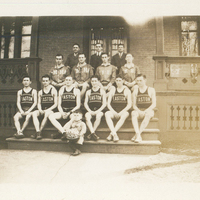 """Six young men wearing Easton basketball jerseys sitting on stairs. A small boy in front of them is holding a basketball with """"1928-29"""" written on it."""