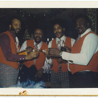 Four men wearing red vests with drinks in hand.