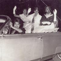 A group of women that wear formal dresses driving on a car and waving their hands.