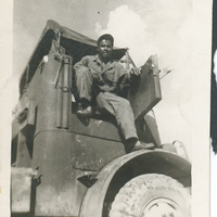 A man sitting in a truck with the door open.