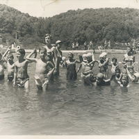 Several children and adults standing in a pool. Some children are holding hands above water.