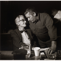 Two men looking at each other. The elderly man on the left, wearing glasses and a bowtie, is seated. The other man is younger and is standing with his right arm around the elderly man. Their hands touch on the table in front of them.