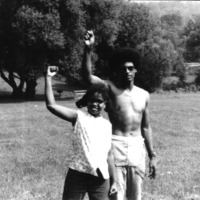 Naked torso man and a girl with glasses standing together with raised hands.