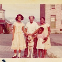 Family and a dog standing in front of a house.