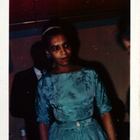 A woman wearing a blue holiday dress and tiara.