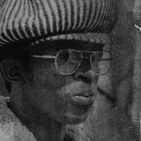A headshot of a man wearing glasses and a striped cap.