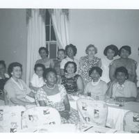 Several women in formal wear. Some are seated at a table while others are standing in front of a wall.
