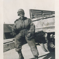 A man in military fatigues sitting on top of a drawbar. He is holding a handgun.