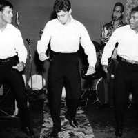Band musicians in white shirts dance on a scene.