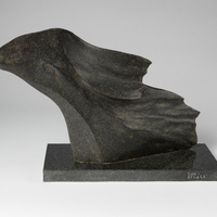 A curved granite sculpture. The underside looks smooth, while the upper surface is rippled and jagged, which resembles a wave.