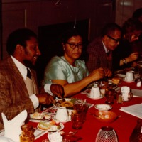 A group of men and women in holiday dresses sit and eat at the festive table.