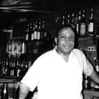 A man wearing white shirt stand in front of a bar counter.