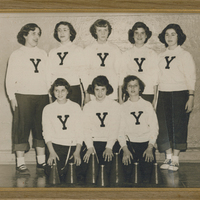 """Three girls kneeling while five girls stand behind them. They are all wearing white shirts with the letter """"Y"""" on them."""