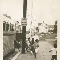 Several children boarding a bus.