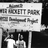 Two boys (one with baseball bat) standing under a sign.