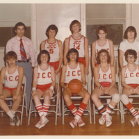 Two rows of teenage basketball players. Team members in the front row are sitting while those in the back are standing.