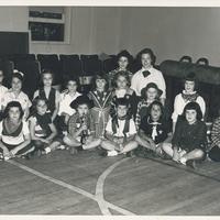 Several girls dressed as cowboys sitting cross-legged.