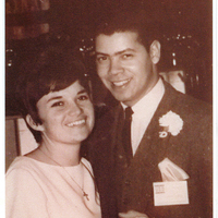 A man in a suit holding hands with a woman in a white dress. Both are smiling.