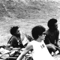 Three men sitting on the ground.